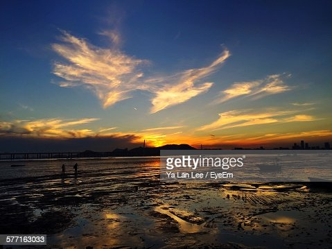 Scenic View Of Wet Shore Against Sky