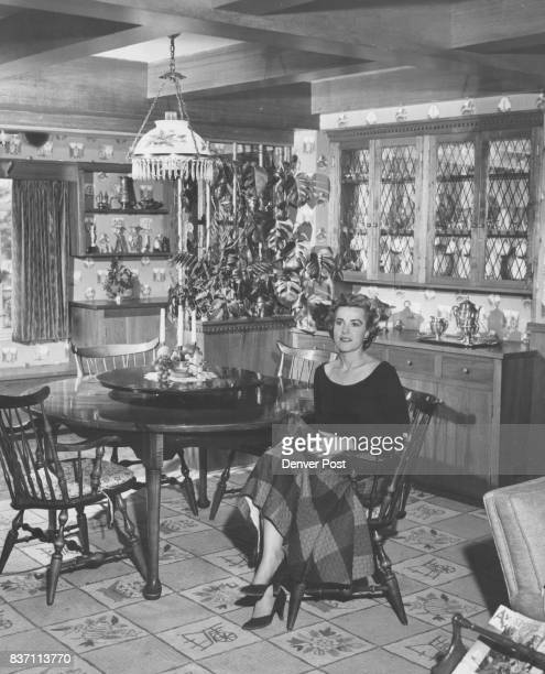 Scenic wallpaper and an almostmatching rug are the background accents for the mellow pine furniture used in the dining area of Mrs Lewis Hayden's...