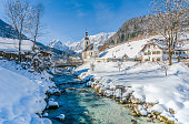 Panoramic view of scenic winter landscape in the Bavarian Alps with famous Parish Church of St. Sebastian in the village of Ramsau, Nationalpark Berchtesgadener Land, Upper Bavaria, Germany.
