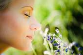 Close up portrait of a woman, with eyes closed and with a gentle smile on her face, smelling lavender on warm Summer day. Joy and scent of Summer concept. Selective focus, natural light,blurred backgr