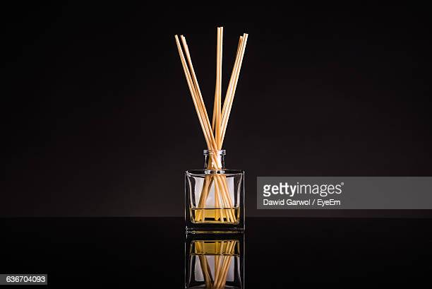 Scented Sticks In Bottle With Reflection Against Black Background