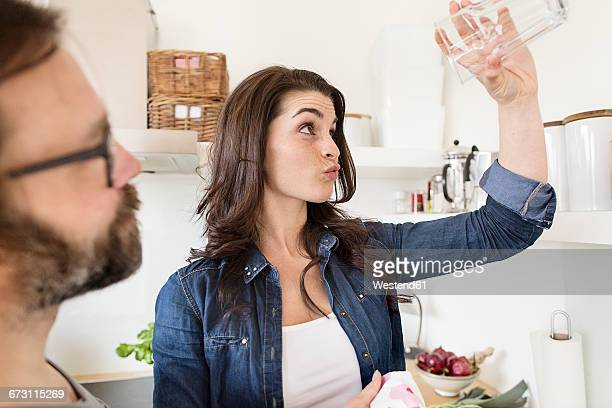 Sceptical woman in kitchen holding up glass