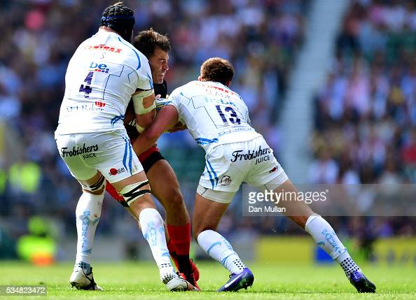 Schalk Brits of Saracens is tackled by Mitch Lees and Henry Slade of Exeter Chiefs during the Aviva Premiership final match between Saracens and...