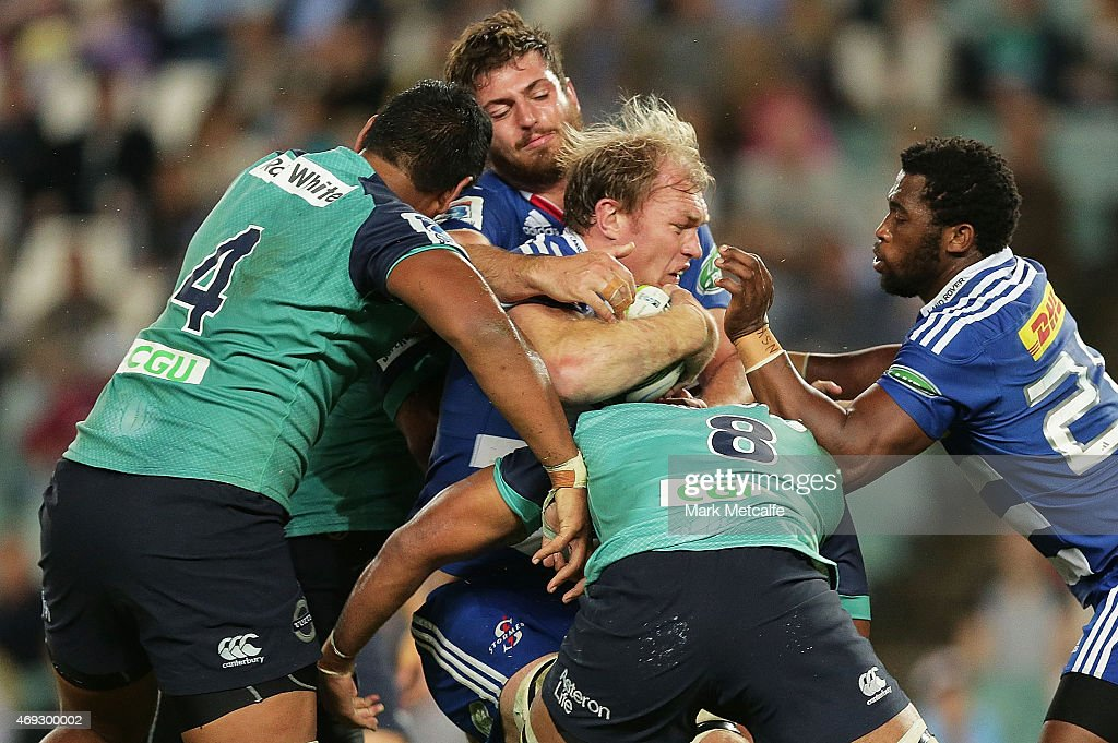 Schalk Burger of the Stormers is tackled by Wycliff Palu and Will Skelton of the Waratahs during the round nine Super Rugby match between the Waratahs and the Stormers at Allianz Stadium on April 11, 2015 in Sydney, Australia.