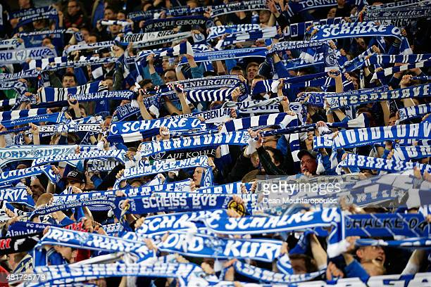 Schalke 04 fans cheer and show their support for the team by holding up their scarfs during the Bundesliga match between Borussia Dortmund and FC...