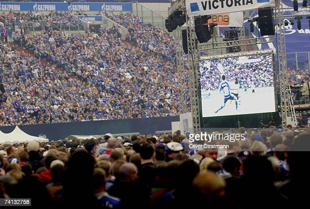 Schalke 04 fans watch play relayed on a giant screen within the crowded stadium during the match between Borussia Dortmund and Schalke at the Veltins...