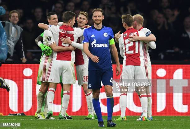 Schalke's defender Benedikt Hoewedes reacts in front of celebrating Ajax players after the UEFA Europa League football match between Ajax Amsterdam...