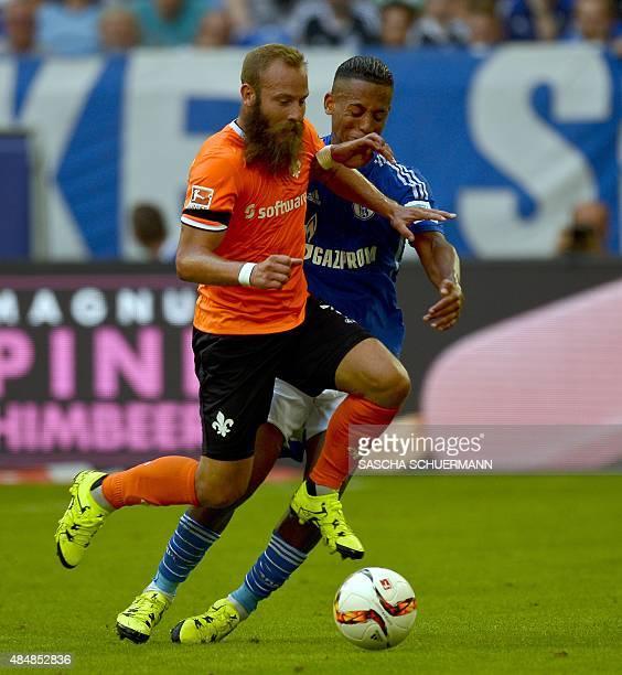 Schalke's defender Dennis Aogo and Darmstadt's midfielder Marcel Heller vie for the during the German first division Bundesliga football match FC...