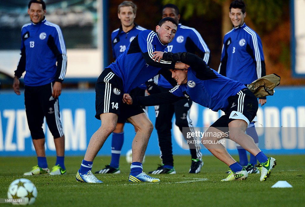 Schalke's Greek defender Kyriakos Papadopoulos (C-L) and Schalke's midfielder Lewis Holtby (C-R) warm up during a training session at the training ground, in Gelsenkirchen, western Germany on November 20, 2012, on the eve of the UEFA Champions League football match against Olympiacos Piraeus.