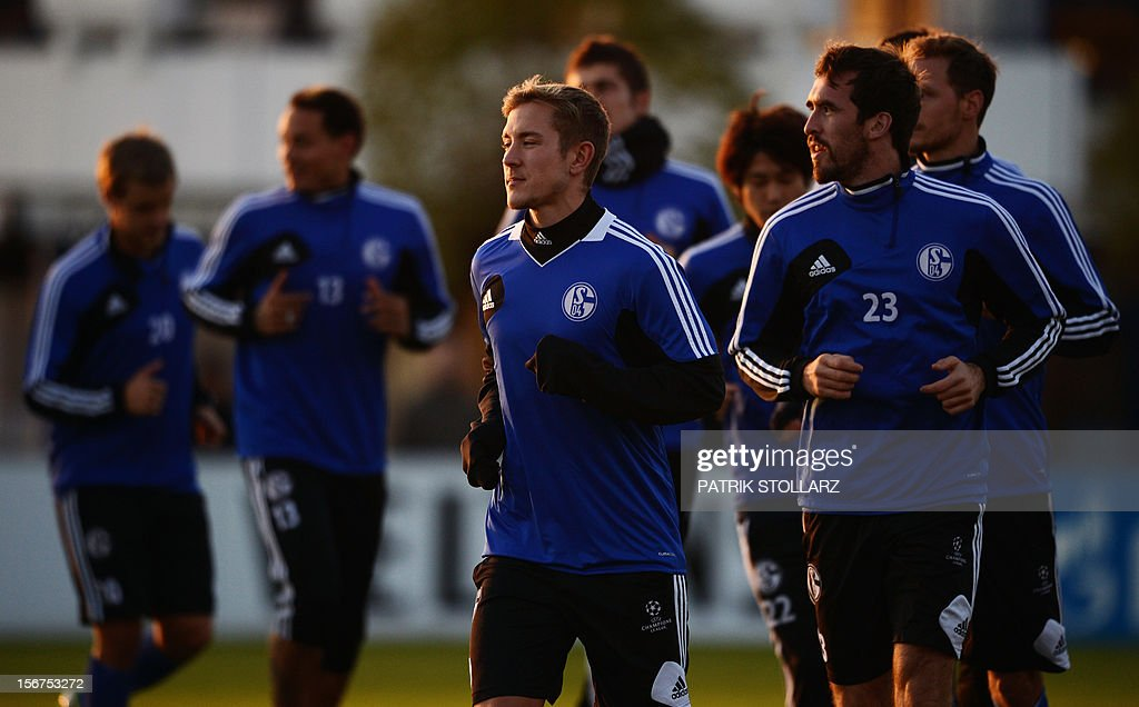 Schalke's players including midfielder Lewis Holtby (C) and Schalke's Austrian defender Christian Fuchs (R) warm up during a training session at the training ground, in Gelsenkirchen,western Germany on November 20, 2012, on the eve of the UEFA Champions League football match against Olympiacos Piraeus.