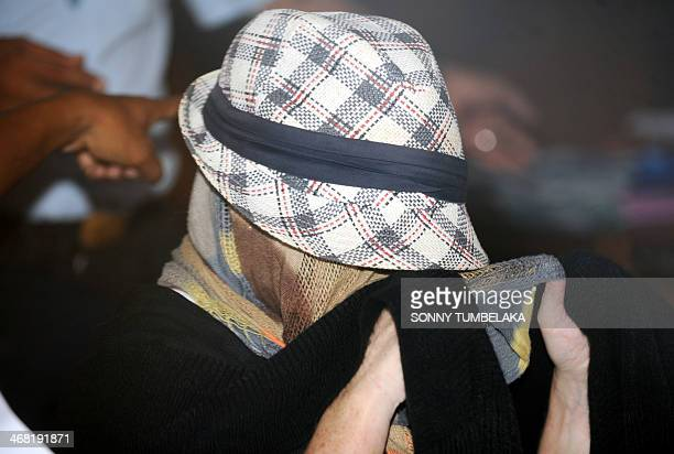 Schapelle Corby is seen with her face covered at a correction bureau in Denpasar on Indonesia's resort island of Bali on February 10 2014 The...