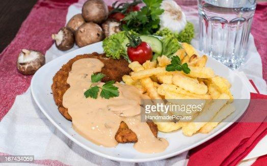 Milanesa con papas fritas y una salsa : Foto de stock