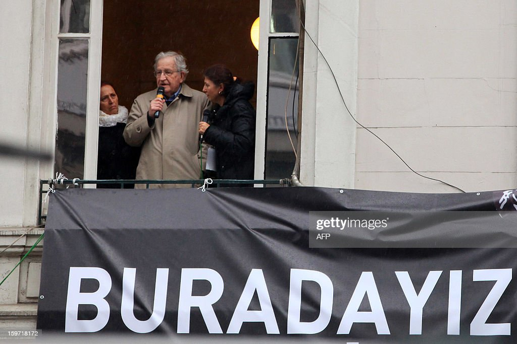 US scholar and activist Noam Chomsky (C) speaks on the balcony of the offices of Armenian newspaper 'Agos' during a commemoration ceremony for slain journalist Hrant Dink ,in Istanbul, on January 19, 2013. Dink, one of the most prominent voices of Turkey's shrinking Armenian community, was killed by a gunman on January 19, 2007. The 52-year-old Dink, a prominent member of Turkey's tiny Armenian community, campaigned for reconciliation but was hated by Turkish nationalists for calling the World War I massacres of Armenians a genocide.