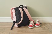 School backpack and sneakers on the floor in a home interior