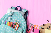 School backpack with coloured pencil and school supplies on pink paper background. Back to school concept.
