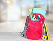 School bag rucksack backpack on table indoors empty space background. School supplies.