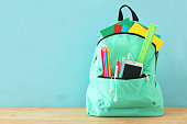 school bag with stationery and notebooks in front of wooden blue background. Back to school concept