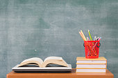 School books on desk, Back to school supplies. Books and blackboard on wooden background, education concept