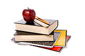 A stack of school books and spiral notebooks with a pencil and a ruler on top in front of a white background with an apple