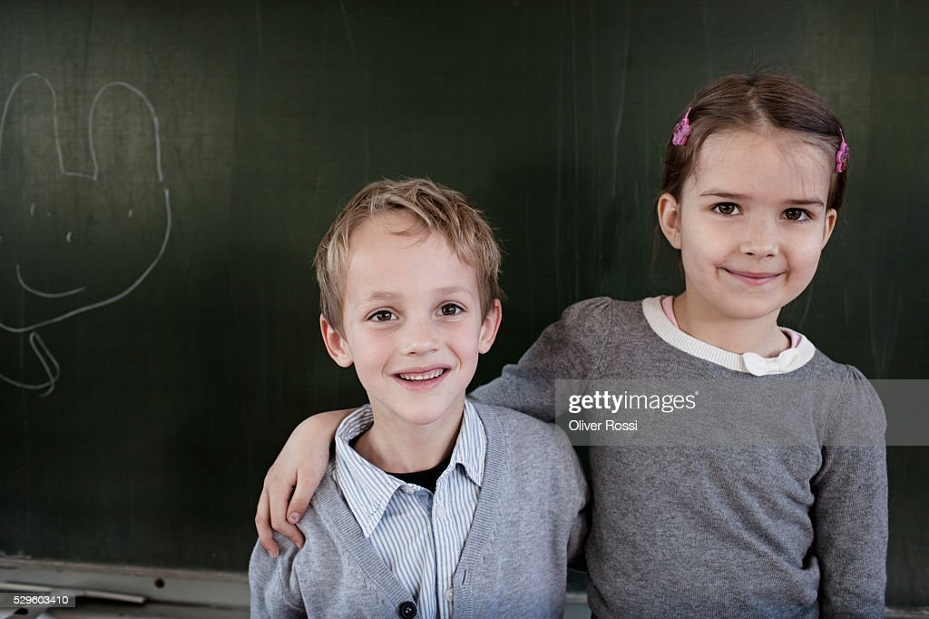 School boy (6-7) and girl (6-7) posing in front of blackboard : Stockfoto