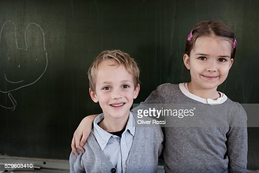 School boy (6-7) and girl (6-7) posing in front of blackboard : Foto stock