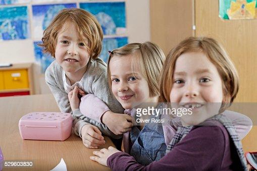 School boy (6-7) and two schoolgirls (6-7) sitting together in classroom : Foto de stock