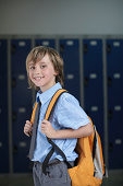 School boy holding backpack