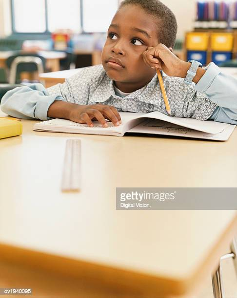 School Boy Sits at a Table With an Exercise Book, Listening and Looking Sideways