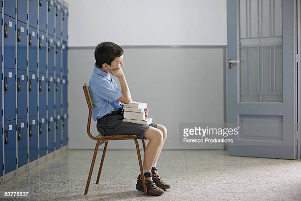School boy sitting with books