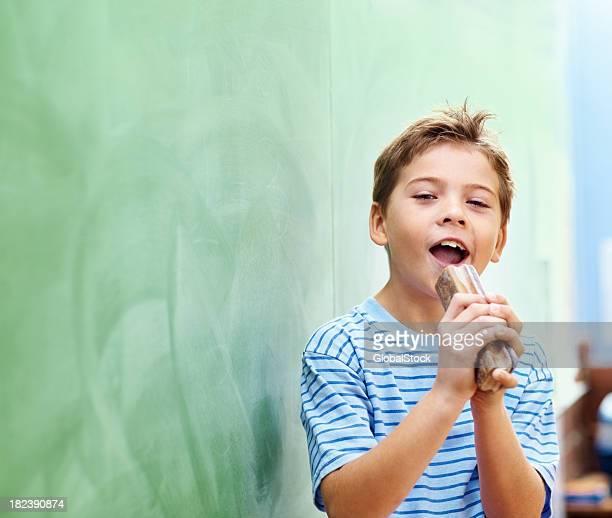 Garçons de l'école avec un plumeau comme mike de sing