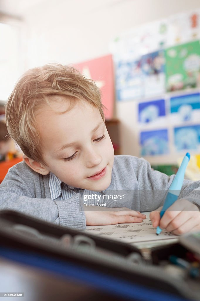 School boy (6-7) writing in classroom : Stock Photo