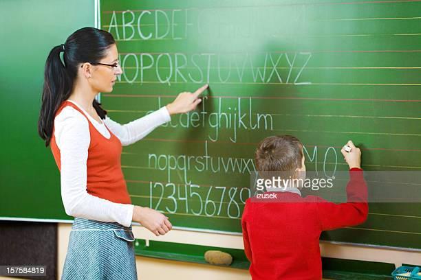 School Boy Writing On Blackboard