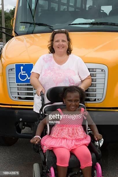 driver bus della scuola sta dietro sua studente in sedia a rotelle