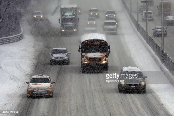 A school bus drives along a highway in a snow storm in Brooklyn on March 5 2015 in New York City New York City and much of the Northeast is...