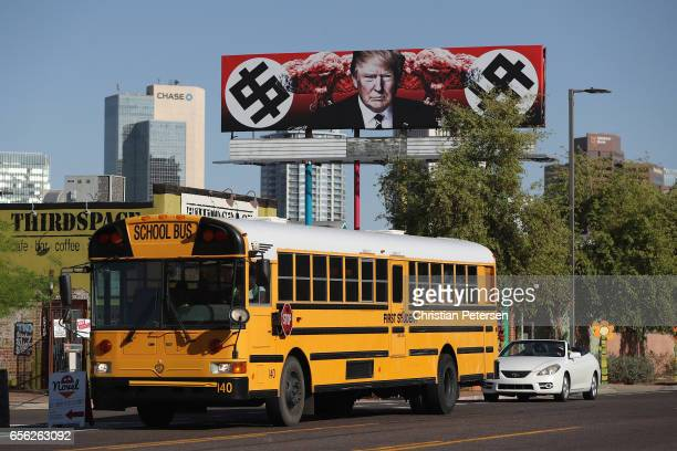 A school bus drives past an antiTrump billboard displaying swastikalike dollar signs near the corner of Grand Ave and Taylor Street on March 21 2017...