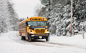A school bus drives down a snow covered rural country road lined with snow covered trees after a snow storm during the winter season.  Series 3 of 3
