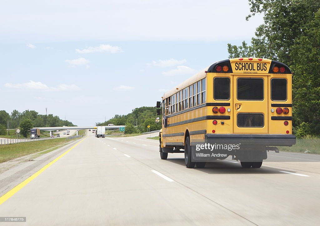 School bus driving down highway : Stock Photo