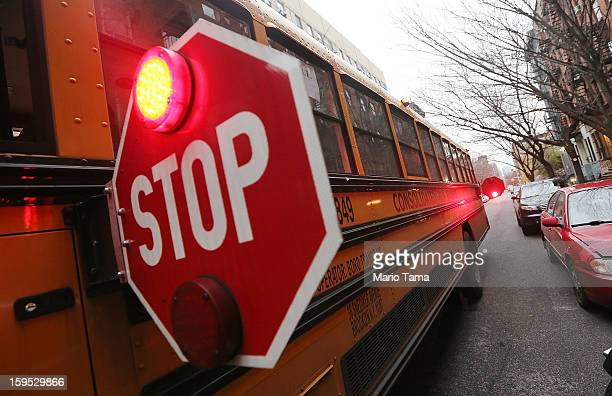 A school bus is stopped while picking up a student in Manhattan's East Village on January 15 2013 in New York City Drivers of the city's school buses...