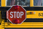 School bus with retracting safety stop sign