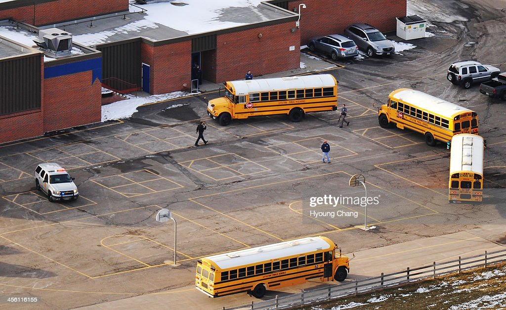 School buses are parked by the Euclid Middle School building, one of the reunification centers for students and parents after a shooting incident at Arapahoe High School. A student carried a shotgun into Arapahoe High School and shot two fellow students in Centennial, Colorado December 13, 2013.