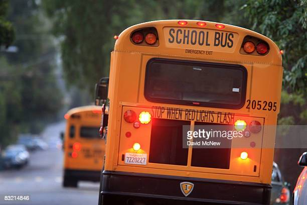 School buses drive down teh road to pick up children before classes begin on October 10 2008 in Pasadena California California State Treasurer Bill...