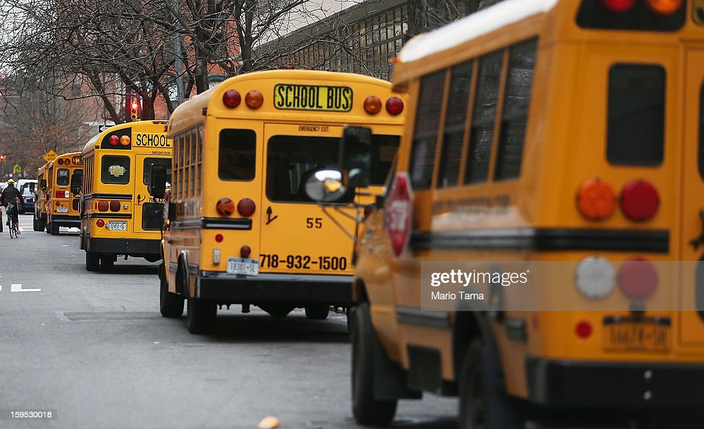 School buses idle in front of a school in Manhattan's East Village on January 15, 2013 in New York City. Drivers of the city's school buses are set to go on strike tomorrow after negotiations with Mayor Michael Bloomberg failed to reach an agreement; over 150,000 children will need to find an alternate method of transportation to school.