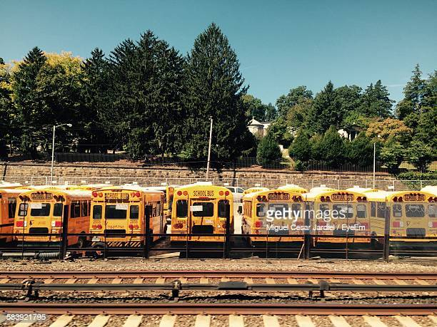 School Buses Parked By Railroad Tracks Against Clear Blue Sky