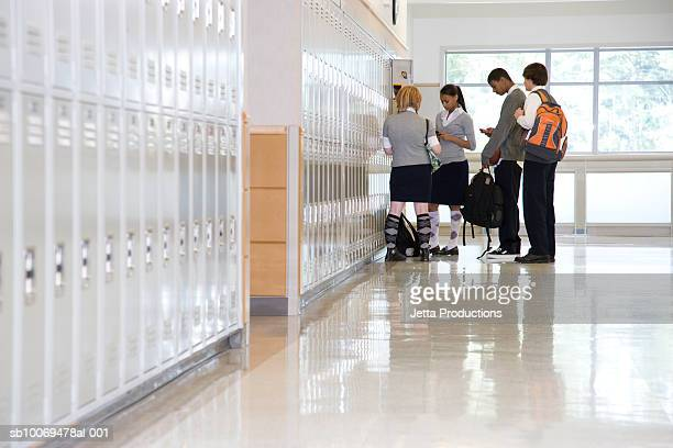 School children by lockers in corridor