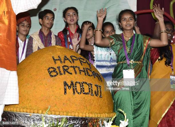 School children cutting a 567 Kg laddoo to celebrate the birthday of Prime Minister Narendra Modi at Constitution Club on September 17 2017 in New...