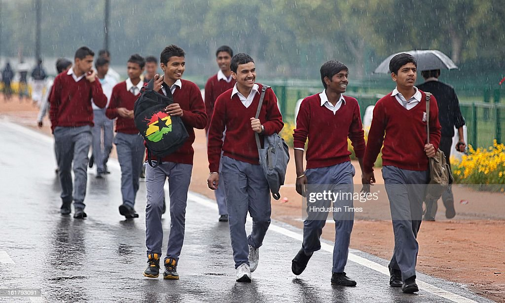 School children enjoying as it rains with overcast sky near India Gate on February 16, 2013 in New Delhi, India. The National capital witnessed a total of 18.6 mm of rains since yesterday and the weather is likely to remain cloudy for another day.
