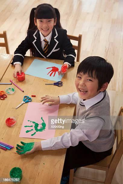 School children finger painting in art class, Beijing