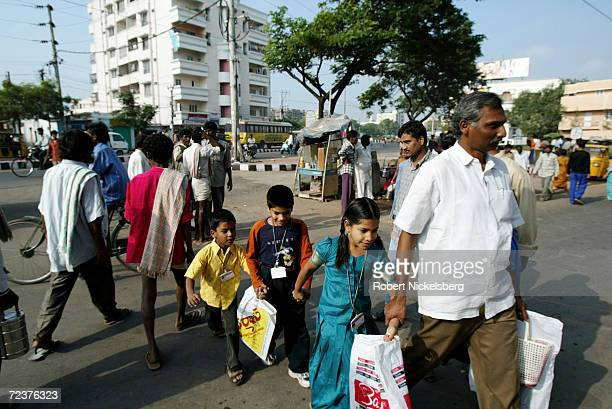 School children from middle class families are led through day laborers at a labor collection point November 8 in Hyderabad India Hyderabad a state...