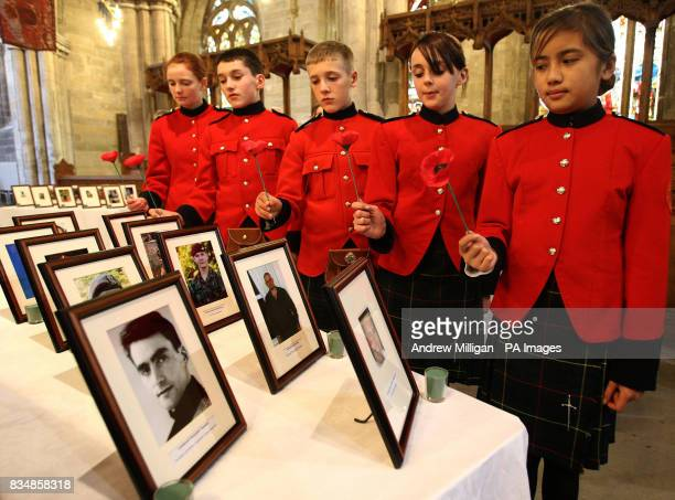 School children from the Queen Victoria School lay poppies beside photographs of soldiers killed in action during a Thanksgiving service rehearsal...