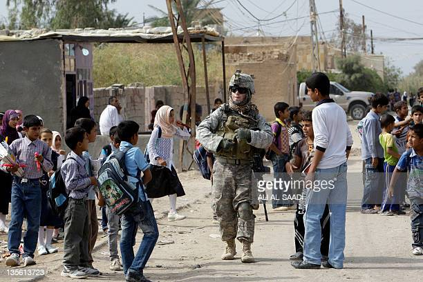 School children gather around a US soldier standing guard outside a public school in the town of Iskandiriyah in Iraq's Babel province 45 kms south...